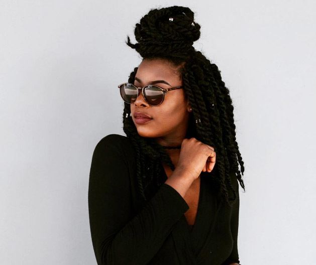 short marley twists styles: the half up half down bun hairstyle as demonstrated by addictedto.og