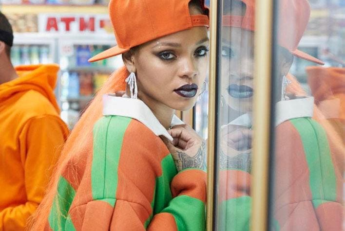 rihanna wearing an orange and green jacket with an orange cap, with her hair styled into an orange low ponytail