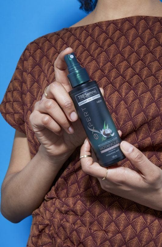 image of a woman holding a bottle of the Tresemme Botanique Hydrating Mist