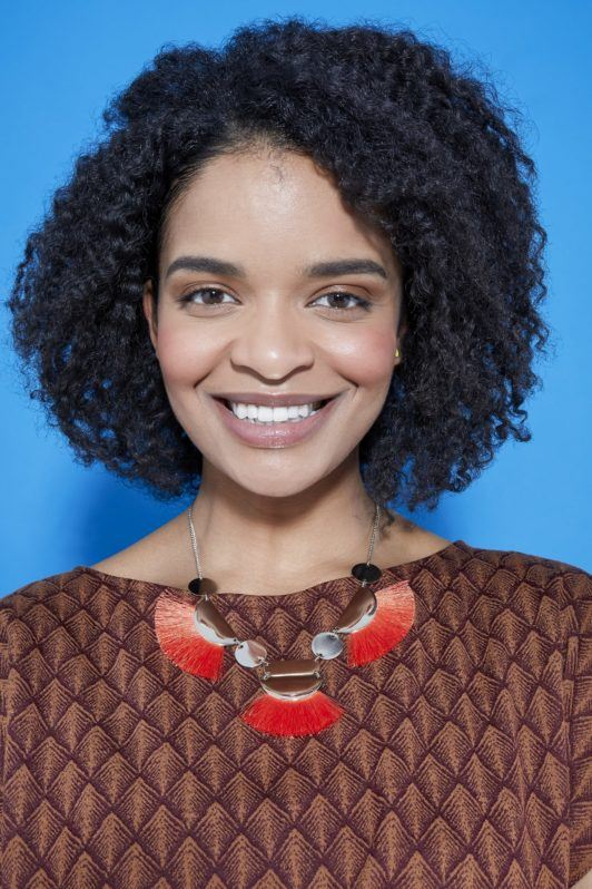 woman with natural curly hair in a bob length cut with a braid out style smiling at the camera