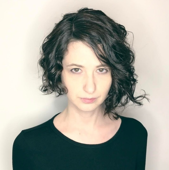 asymmmetrical haircuts: dark haired woman with naturally curly hair