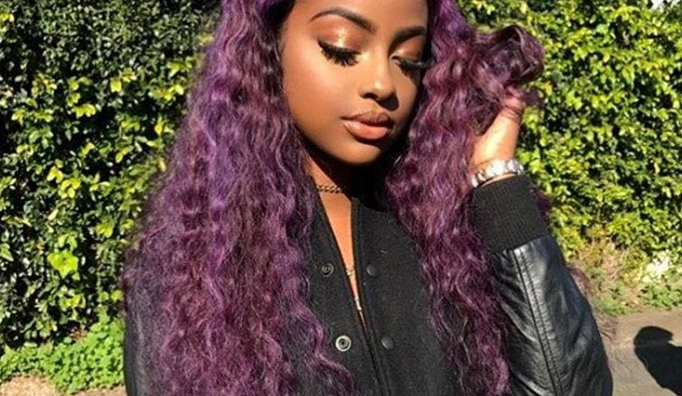 justine sky with long purple curly hair posing outside