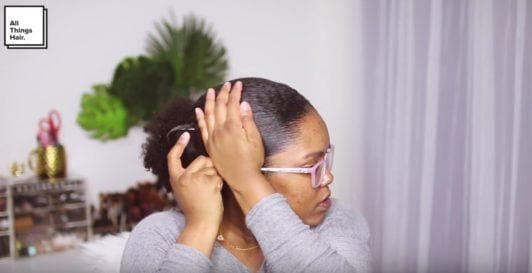 vlogger mini marley brushing her hair into a low puff