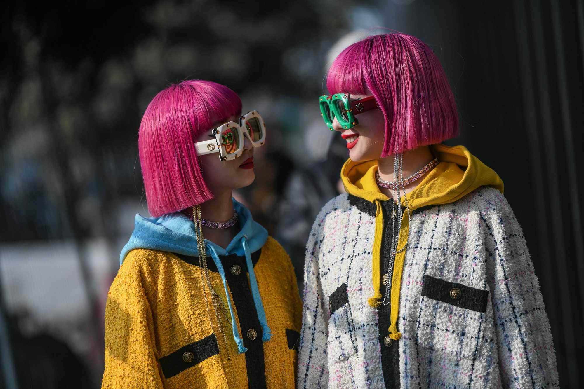 Spring hair colours: Shot of two models with neon pink bob hair, wearing raincoats and sunglasses