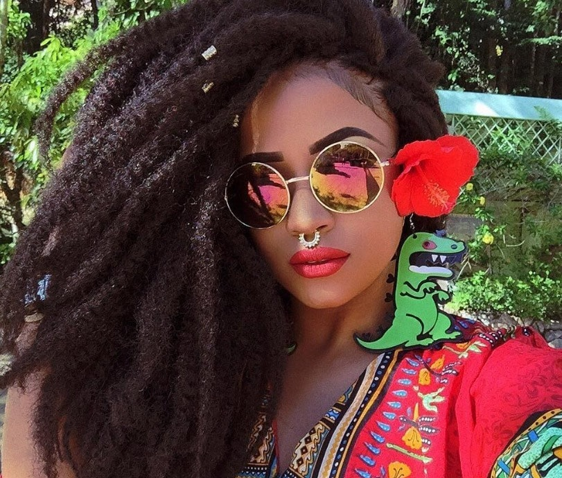 image of a woman with side swept marley twists with flowers and hair cuffs