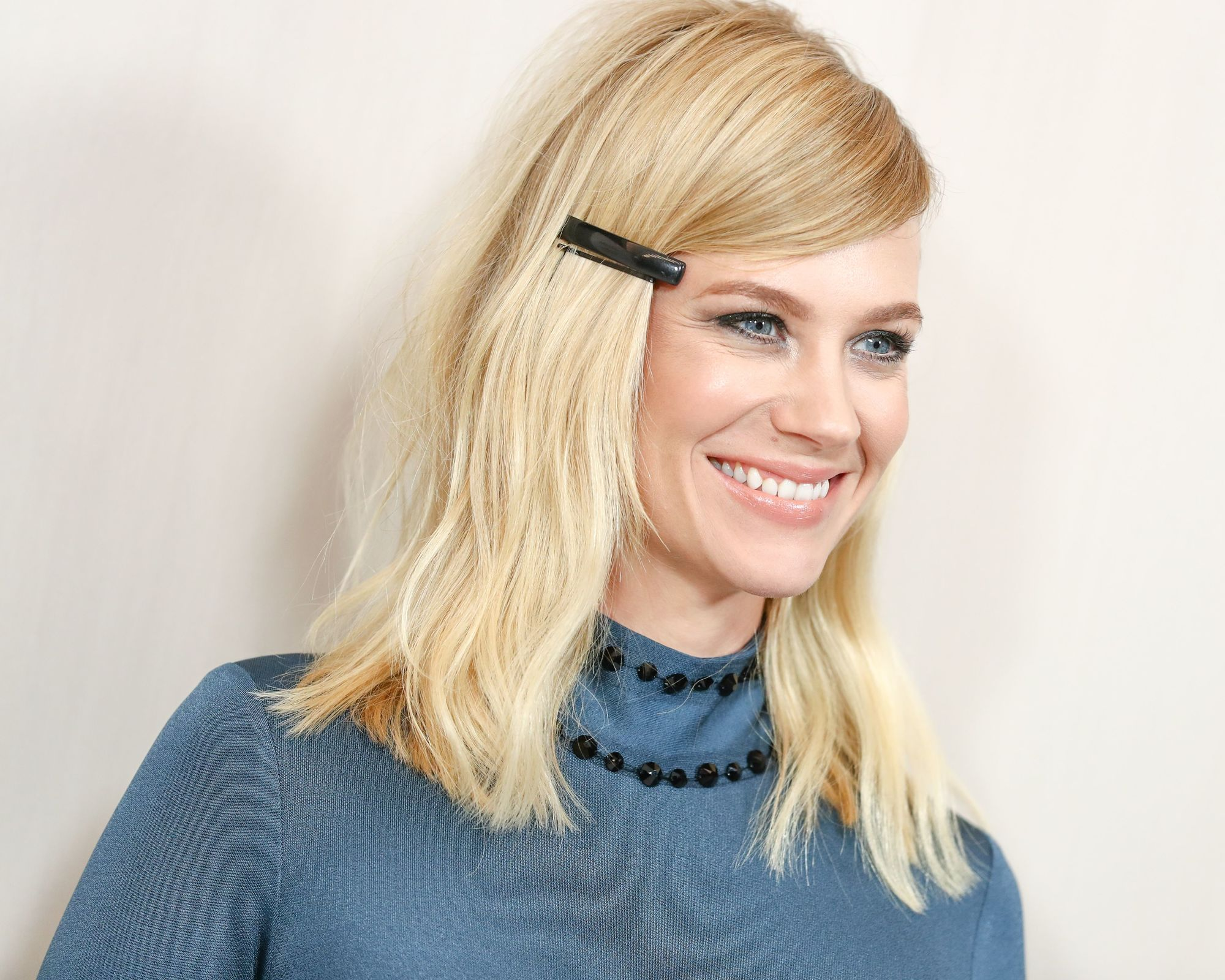 90s hairstyles: image of January Jones with blonde wavy hair, with a hair clips and blue top