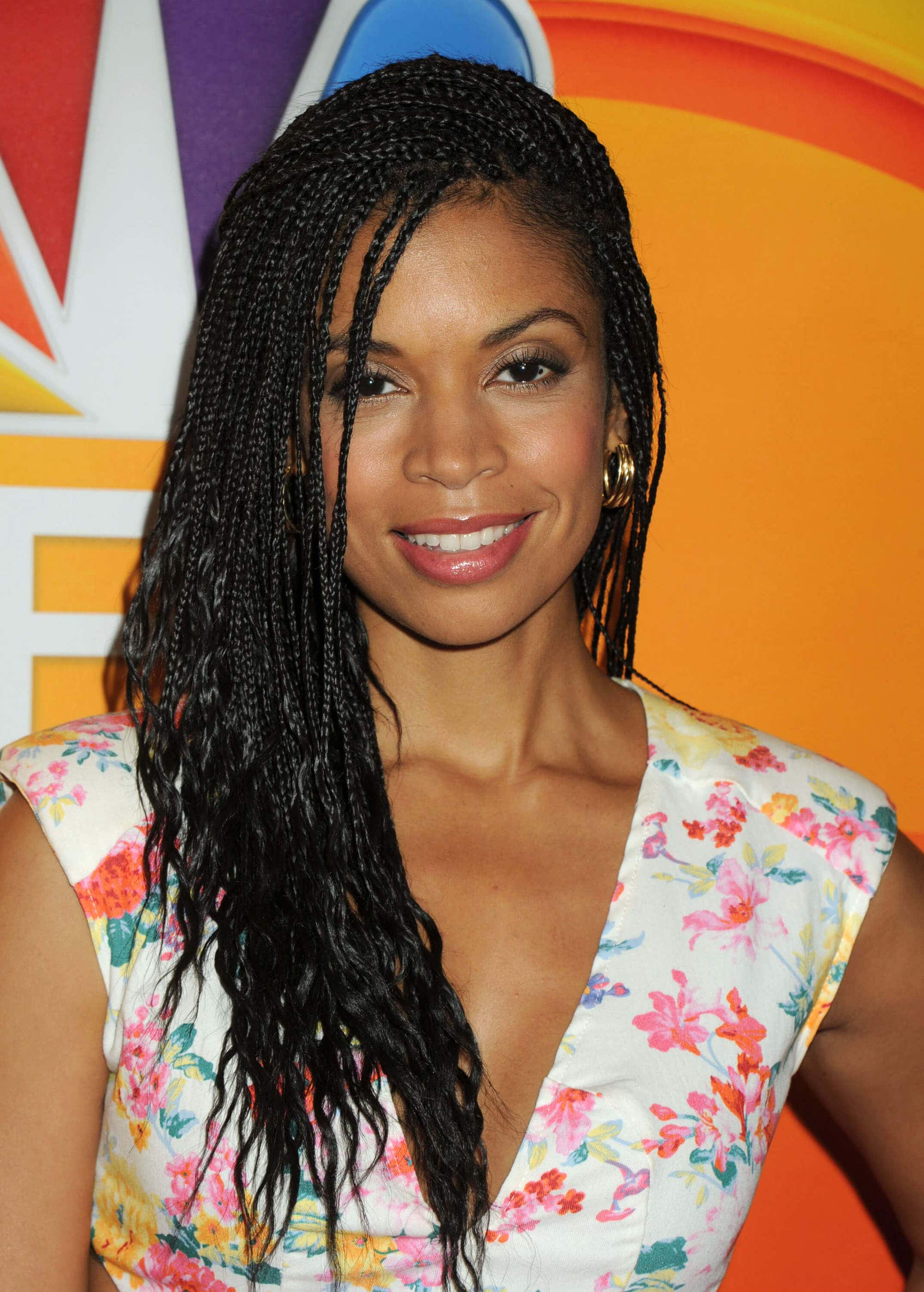 susan kelechi watson with small box braids swept to the side, wearing floral dress