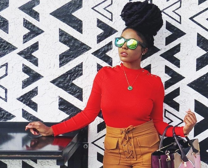 front view of a woman with a high bun updo wearing sunglasses