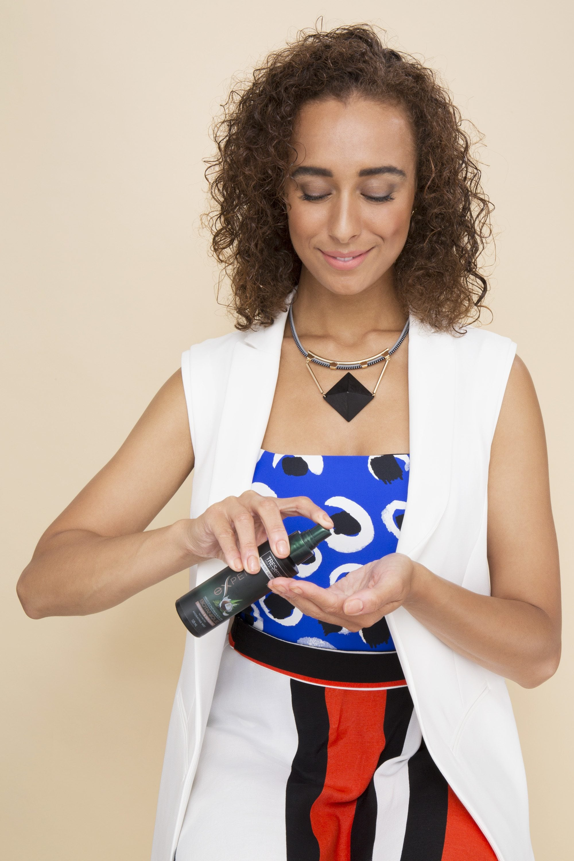Bantu knots - model with brown curly hair adding product