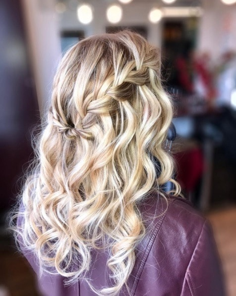 Long curly hair: Close up shot of a woman wearing burgundy leather jacket with her long blonde curly hair in a waterfall braid