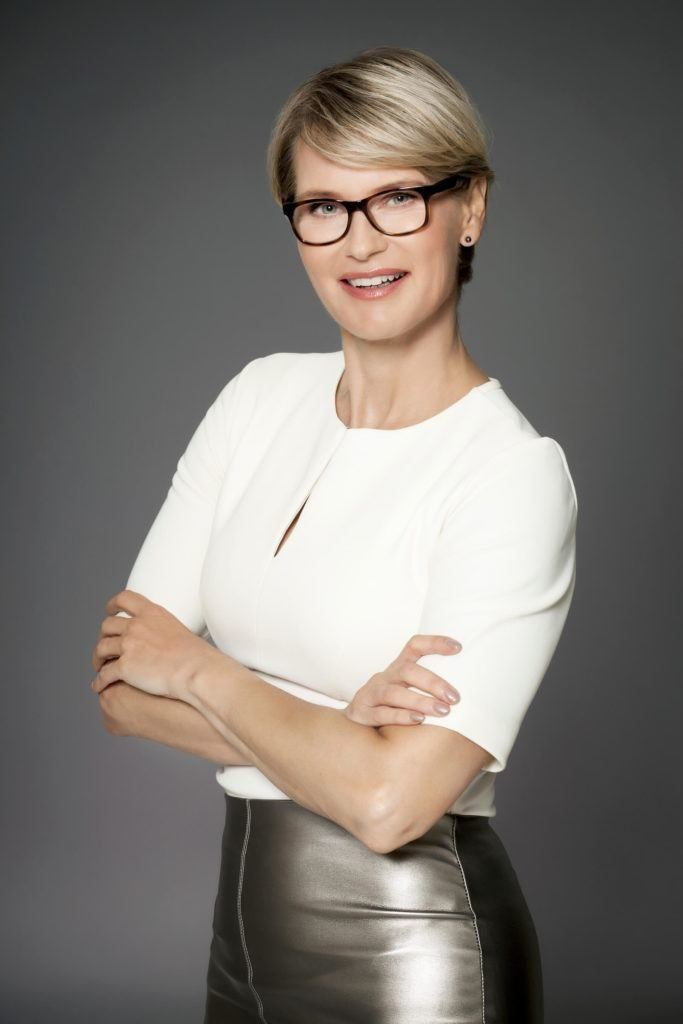 blonde older woman wearing glasses with a sweeping pixie haircut with glasses