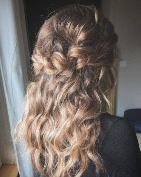 Hairstyles for curly long hair: woman with brunette and blonde curly hair in a boho halo braid