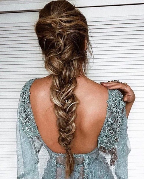 back view image of a woman with her hair in a loose French plait