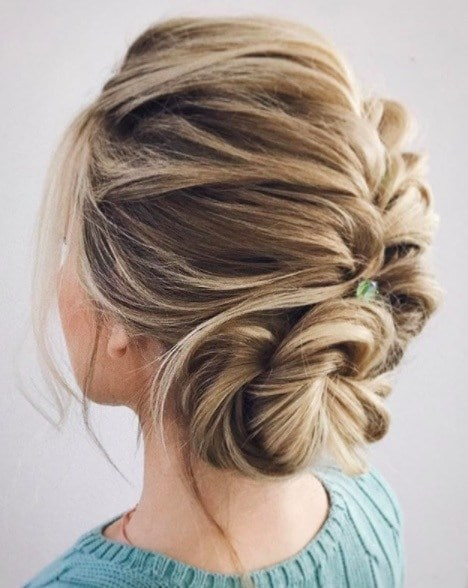 back view of a woman with her hair in a loose French plait hairstyle