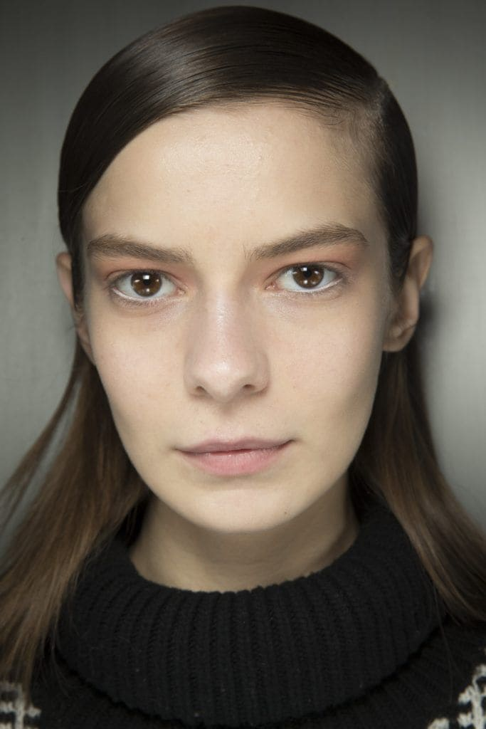 brunette model with androgynous hair in a comb over style