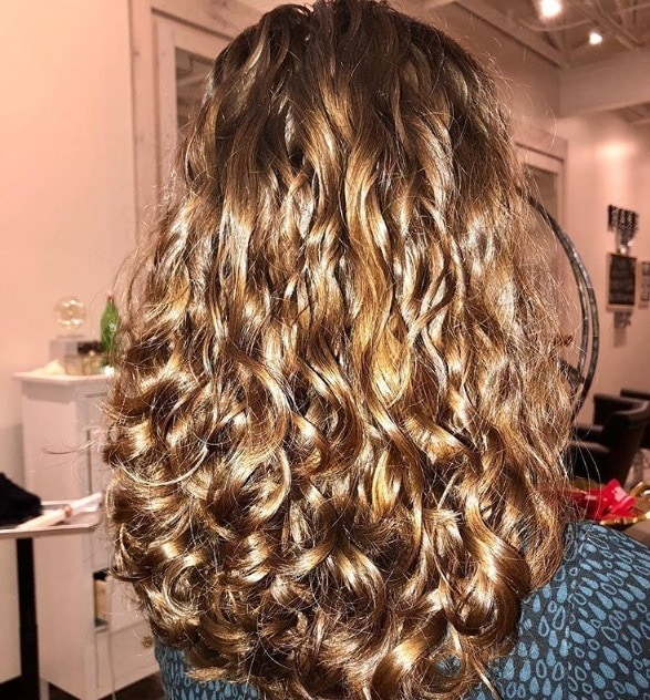 Haircuts for long curly hair: Close up shot of a woman with dark blonde curly hair with long layers in it posing in a salon