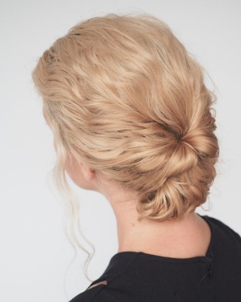 Long curly hairstyles: Blonde woman with curly hair styled into a low chignon