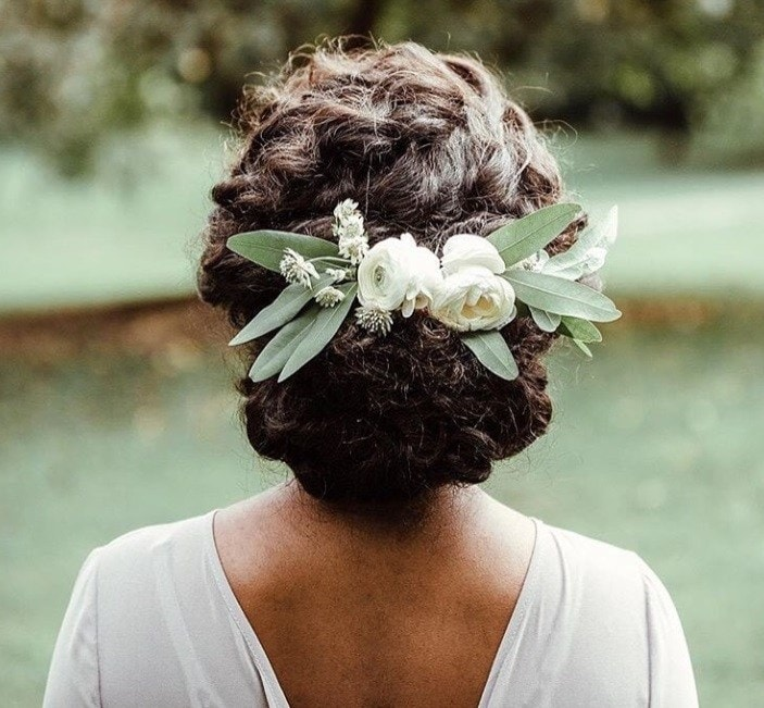 Long curly hair: Close up shot of a woman with dark brown curly hair styled into a curly updo with flowers in it, wearing wedding dress and posing outside