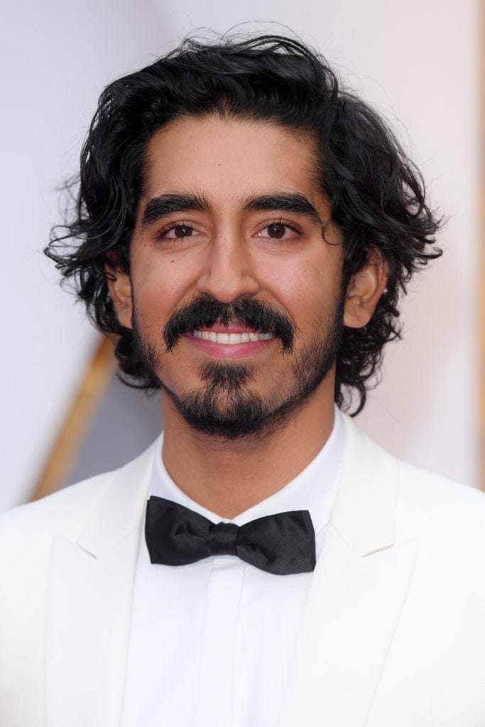 Dev Patel on the red carpet wearing a white suit and black bow tie with his long curly black hair worn undone with some facial hair and a moustache