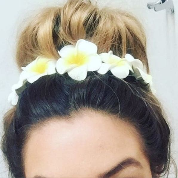 messy bun with flower hair accessories
