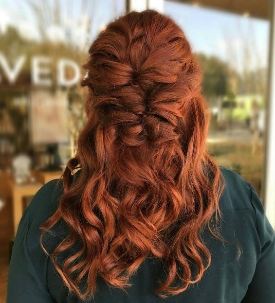 Long curly hair: Close up shot of a woman with long curly ginger hair in a half up pull through braid