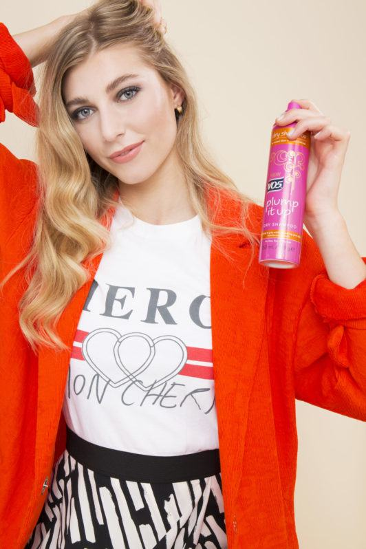 blonde model spraying dry shampoo into her roots