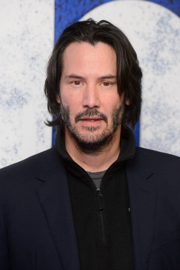 Keanu Reeves on the red carpet wearing a navy blue outfit with his long dark hair worn down with some facial hair