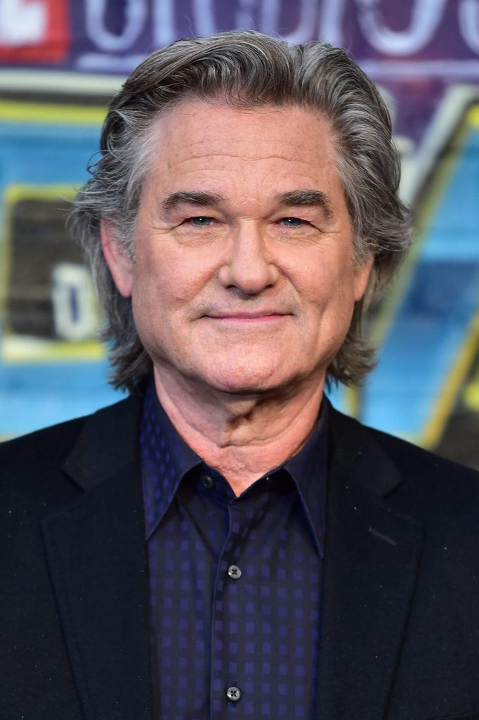 Kurt Russell on the red carpet wearing a blue suit with his long grey hair swept back