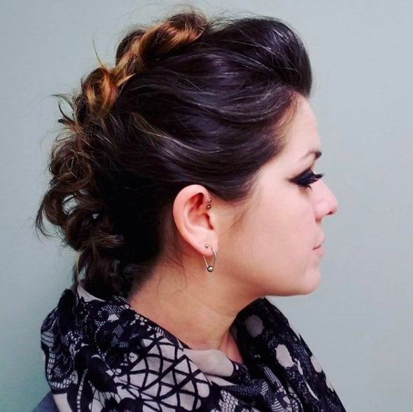 side view of a woman with brunette hair in a mohawk up do hairystyle