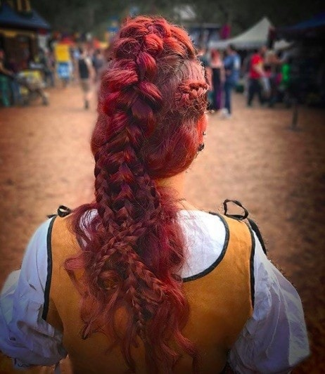 back view of a woman with red hair in a long braided mohawk style