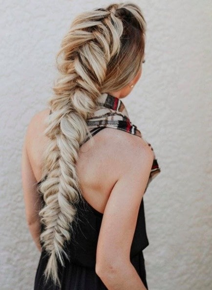 back view of a woman with a long blonde mohawk braid hairstyle