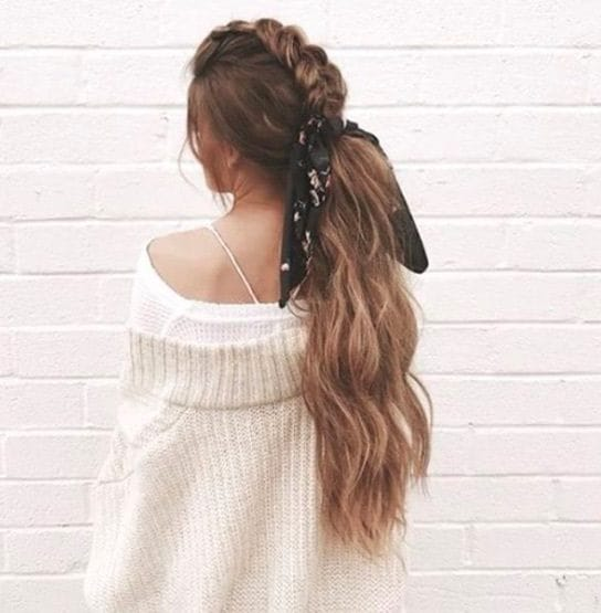 back view of a woman with long brown hair in a mohawk braid style and a low ponytail