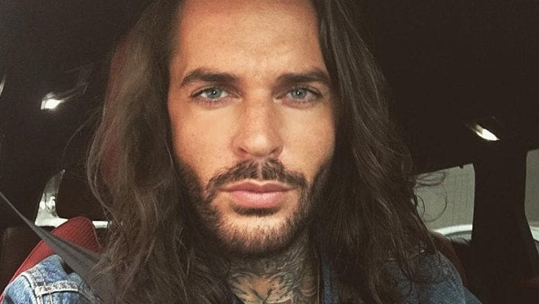 The Only Way Is Essex star Pete Wicks wearing a denim shirt with his long hair worn loose and in waves