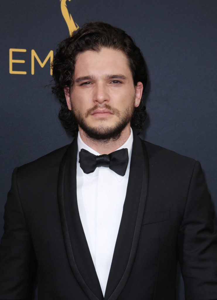 Kit Harington on the red carpet wearing a black suit with a bow tie and his dark brown hair worn long and loose with some facial hair