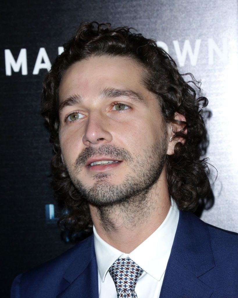 Shia LaBeouf on the red carpet wearing a blue suit with a white shirt and his hair worn long and in curls