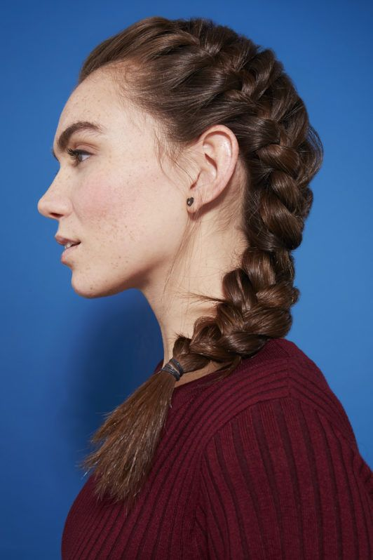 Side French braid how-to: Side profile photo of a brunette woman with long hair in a side French braid, wearing a burgundy knit jumper