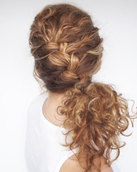 Long curly hair: Woman wearing a white vest top with her long curly hair in a side french braid