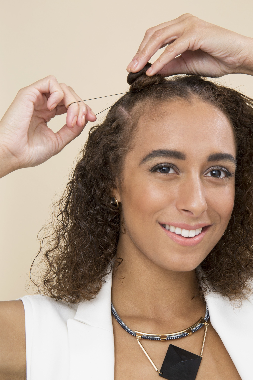 Bantu knots - model with brown curly hair tying elastic around single bantu knot