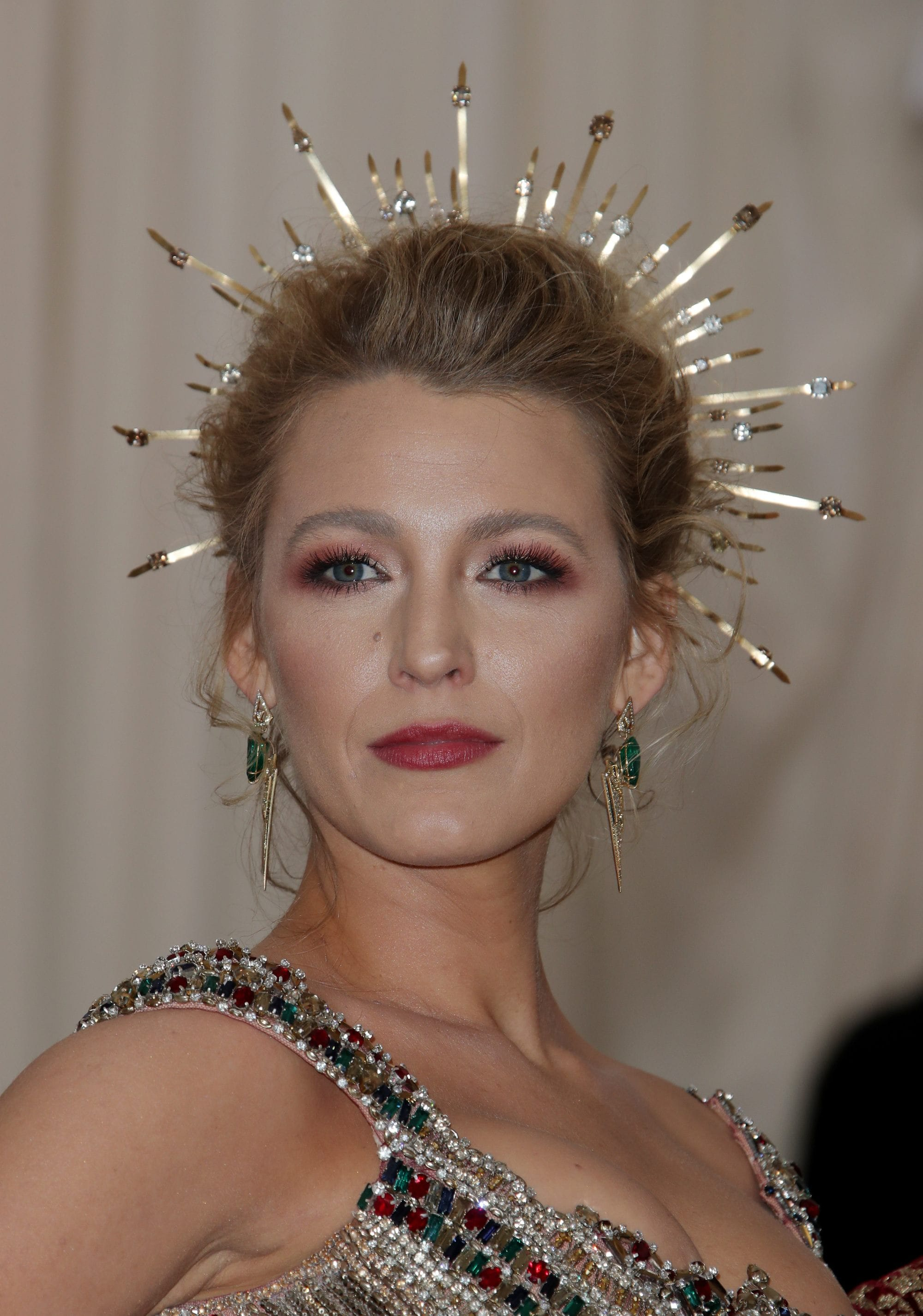 close up shot of blake lively with messy bun updo with halo crown accessory, wearing bejewelled dress and posing on the 2018 met gala red carpet