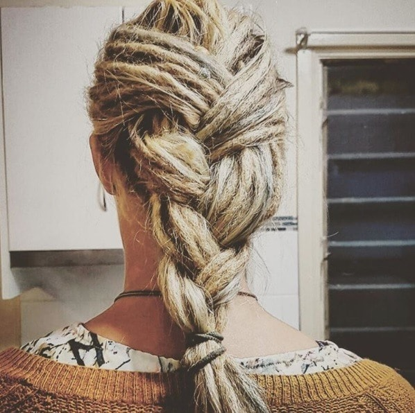 woman with blonde dreadlocks styled into a french plait