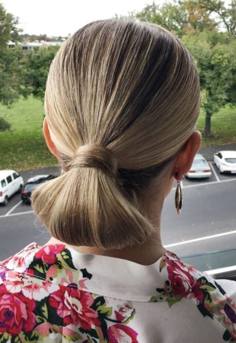 Bridal hairstyles: Woman with golden blonde hair slicked back into a low tuck bun updo