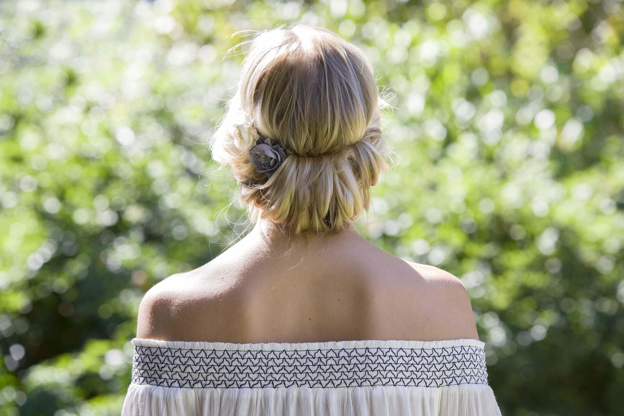 ash blonde: back of a woman's head with blonde hair twisted up into a tuck hairstyle, wearing low-cut bardot top and posing outside