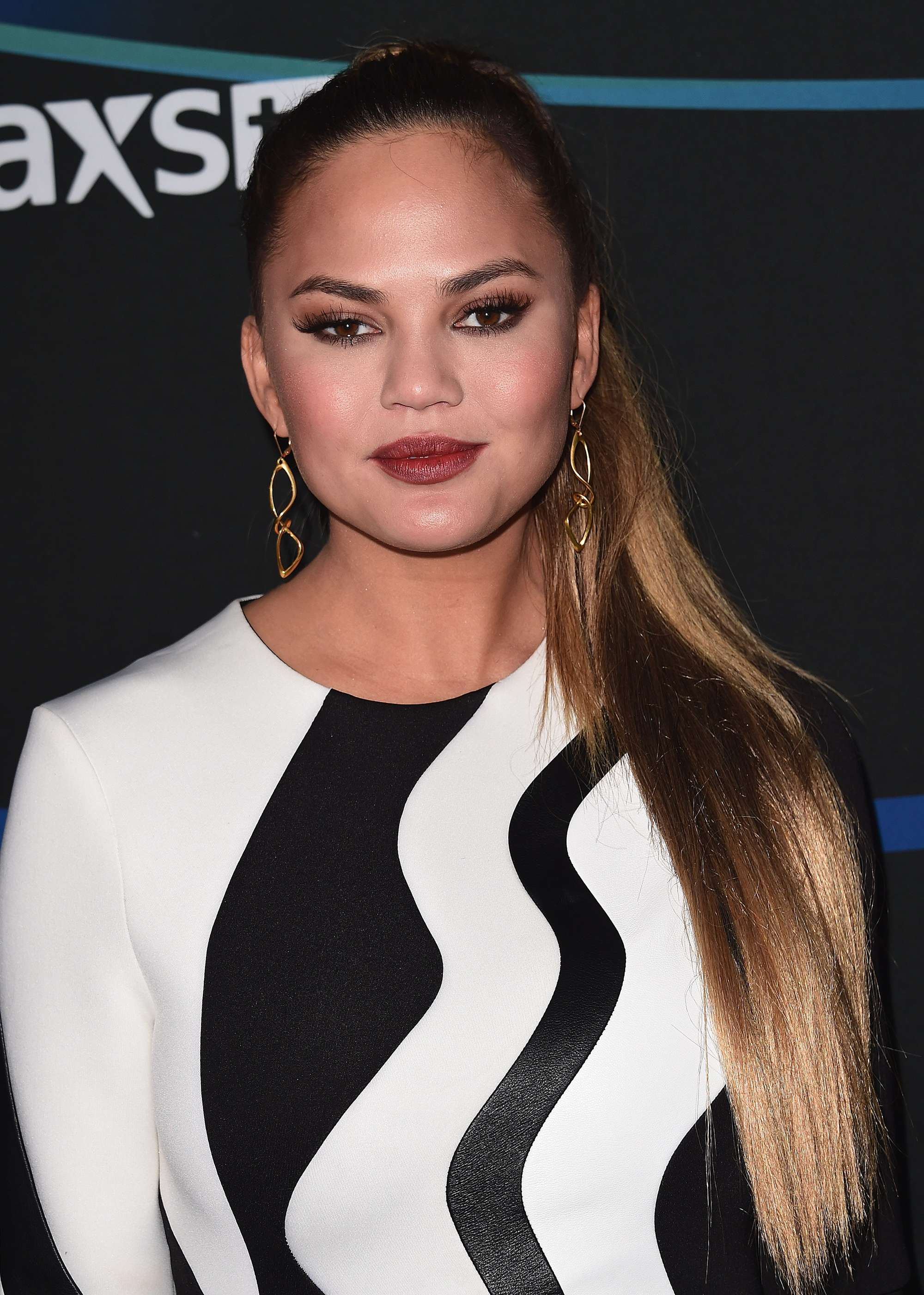 chrissy teigen flatters her round face shape with a high ponytail hairstyle and cool dress at event