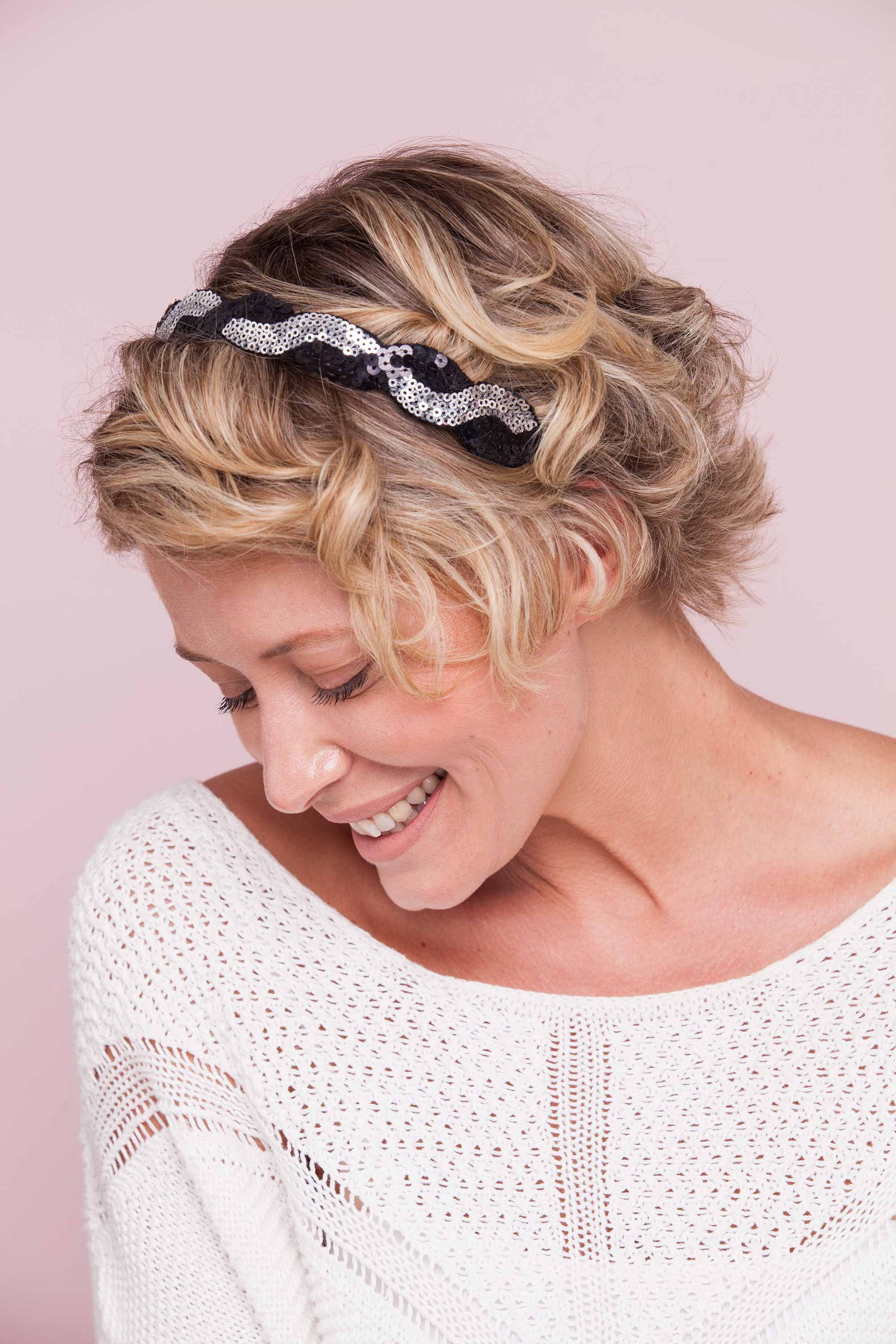 model with headband and beachy waves wearing white and smiling