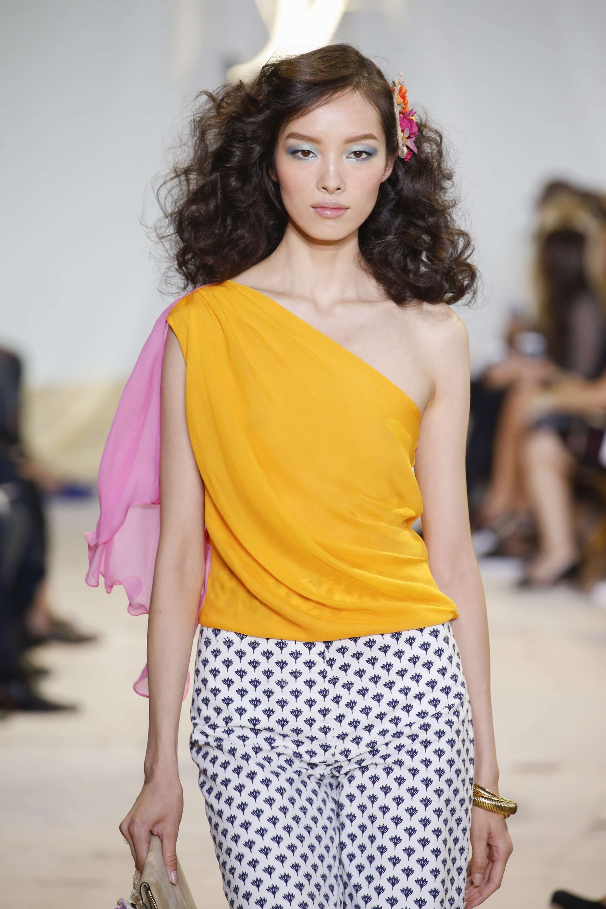 How to use a curling wand: Brunette model on the runway with tight retro waves with a hair clip, wearing a one shoulder yellow top and patterned trousers