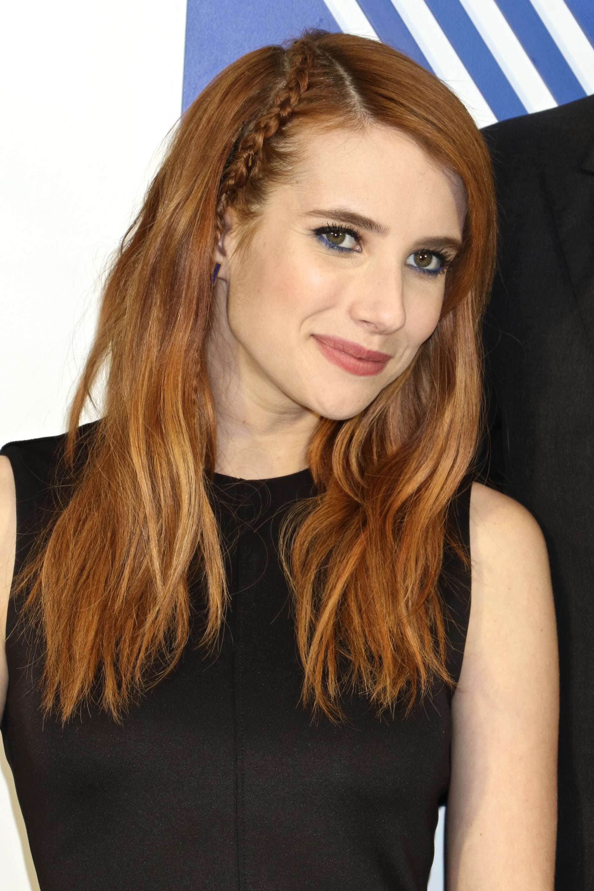 emma roberts with her light auburn hair down with a parting braid