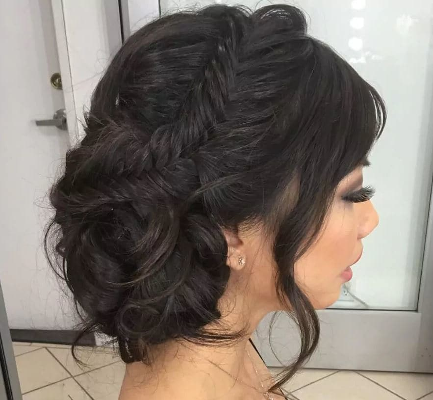 Bridal hairstyles: Fishtail side bun on long dark hair from side profile.