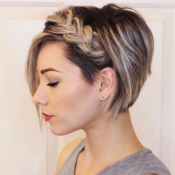 Graduated bob hairstyles: Woman with dirty blonde graduated bob with headband braid, wearing a grey top
