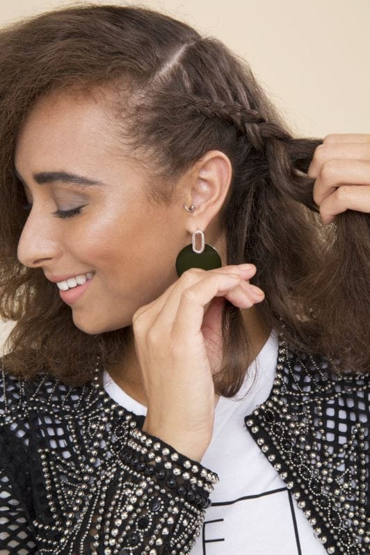 woman with natural curly hair braiding her hair