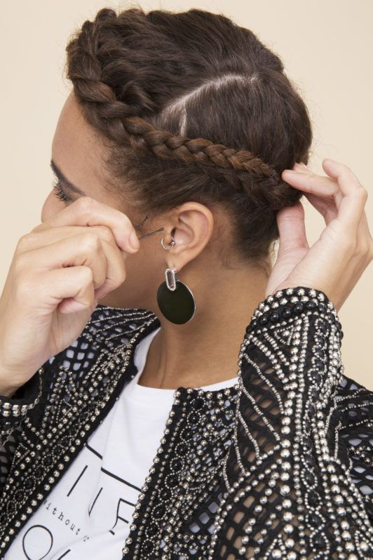 woman with natural curly hair pinning her halo braid in place